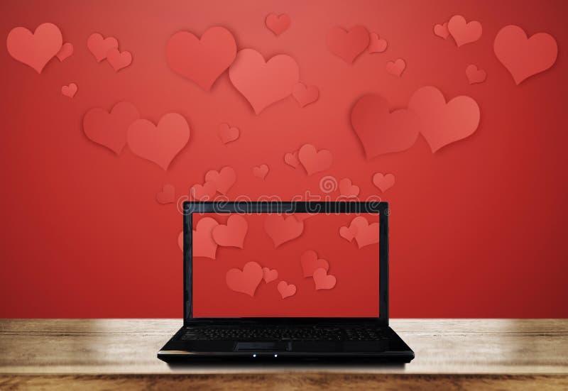 Portátil do computador na mesa de madeira com corações de flutuação no fundo vermelho foto de stock