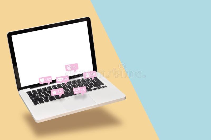 Portátil do laptop com a tela branca vazia com ícones da notificação das interações sociais dos meios com o amigo em social fotos de stock
