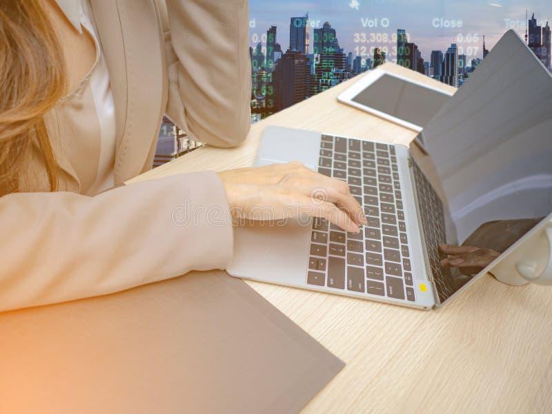 Portátil do uso da mão das mulheres de negócio para o comércio no mercado de valores de ação imagens de stock