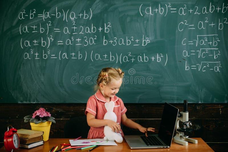 Portátil do uso da menina na lição de datilografia Pouco tipo teclado da criança de portátil na escola Seu assistente pessoal imagem de stock royalty free