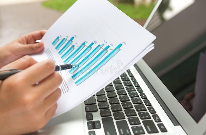 Portátil do uso da pessoa do negócio com diagrama financeiro foto de stock