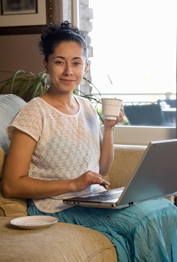 Portátil e café no sofá fotografia de stock royalty free
