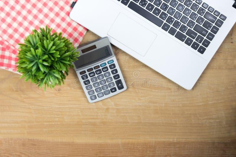 Portátil e calculadora brancos em de madeira fotografia de stock