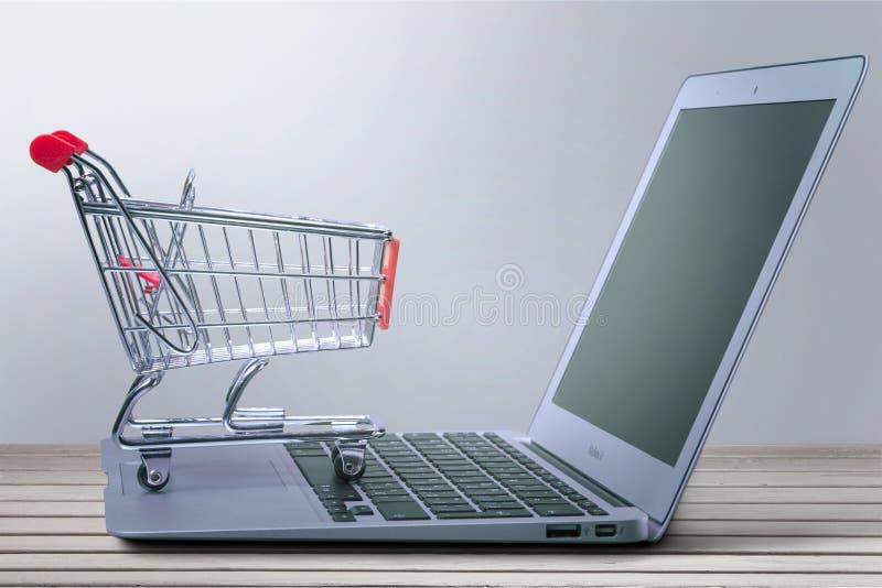 Portátil e carrinho de compras na tabela de madeira fotografia de stock royalty free