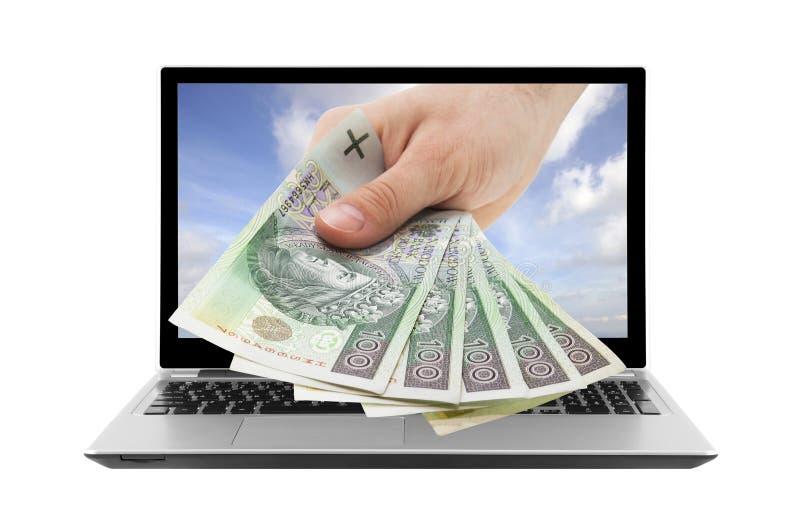 Portátil e mão com dinheiro polonês imagens de stock