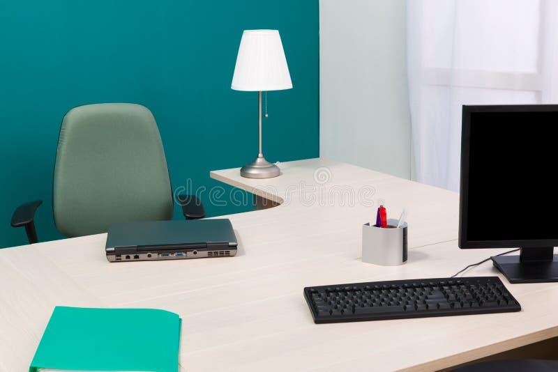 portátil e monitor em uma mesa imagem de stock