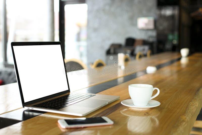 Portátil e telefone celular da tela vazia com a xícara de café na tabela de madeira da barra do café do moderno, janelas grandes  fotos de stock royalty free