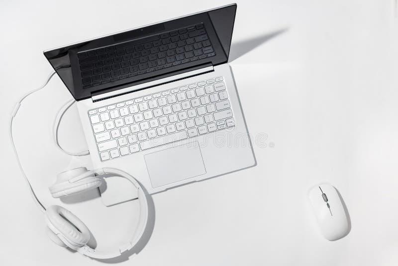 Portátil, fones de ouvido brancos e rato sem fio em um fundo branco Configuração lisa com espaço da cópia foto de stock