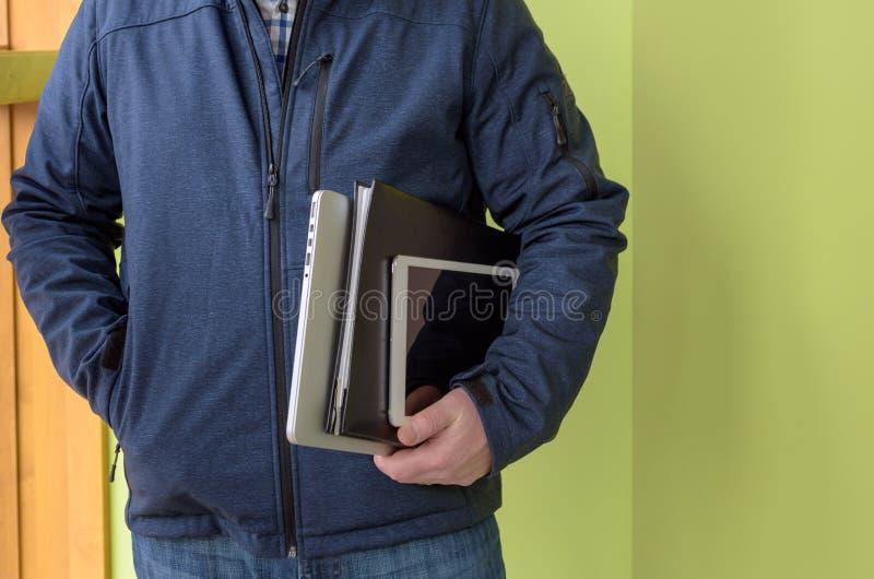 Portátil levando, caderno e tabuleta do homem adulto foto de stock