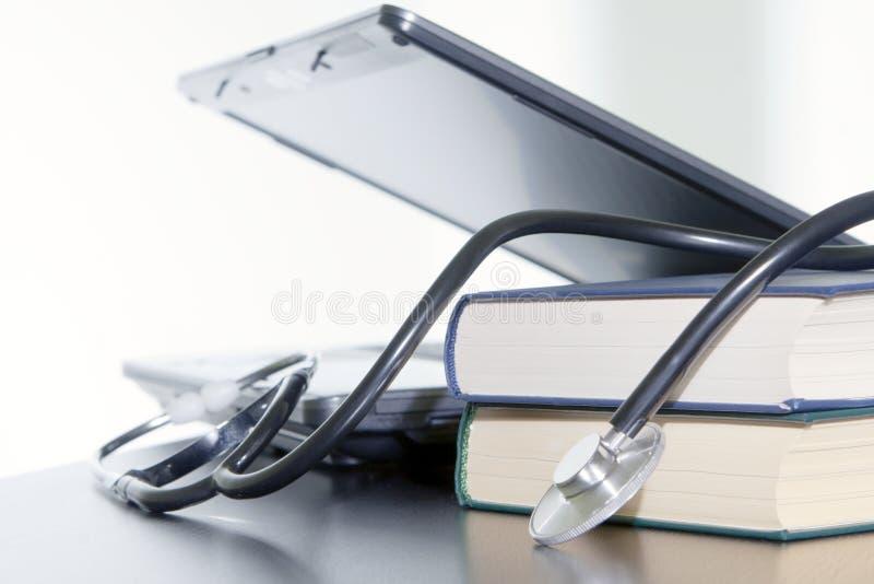 Portátil, livros e estetoscópio médico. imagens de stock