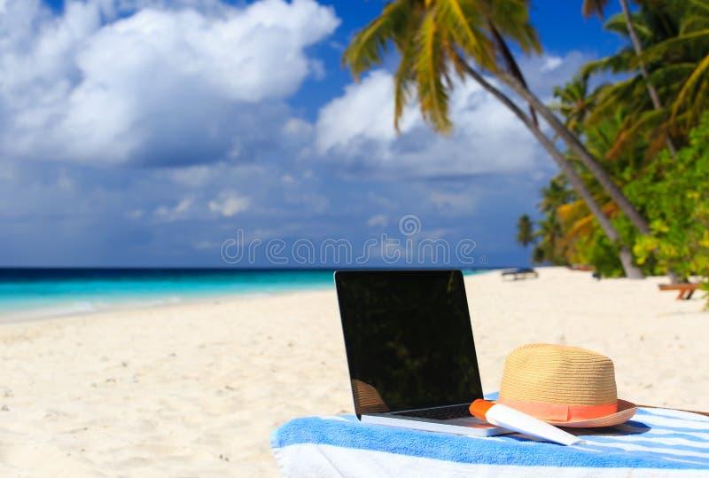 Portátil na cadeira em férias tropicais da praia imagem de stock royalty free