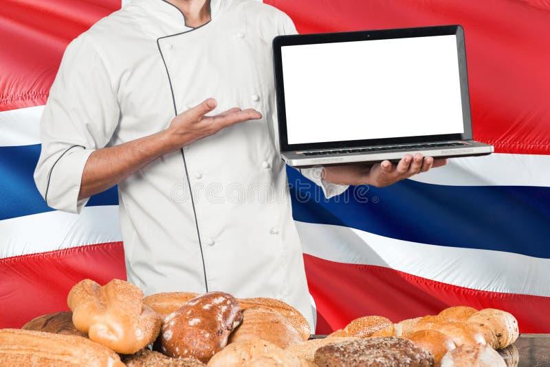 Portátil norueguês da terra arrendada do padeiro na bandeira de Noruega e no fundo dos pães Uniforme vestindo do cozinheiro chefe fotografia de stock