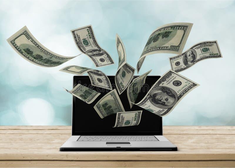 Portátil que faz o conceito do dinheiro no fundo imagens de stock royalty free