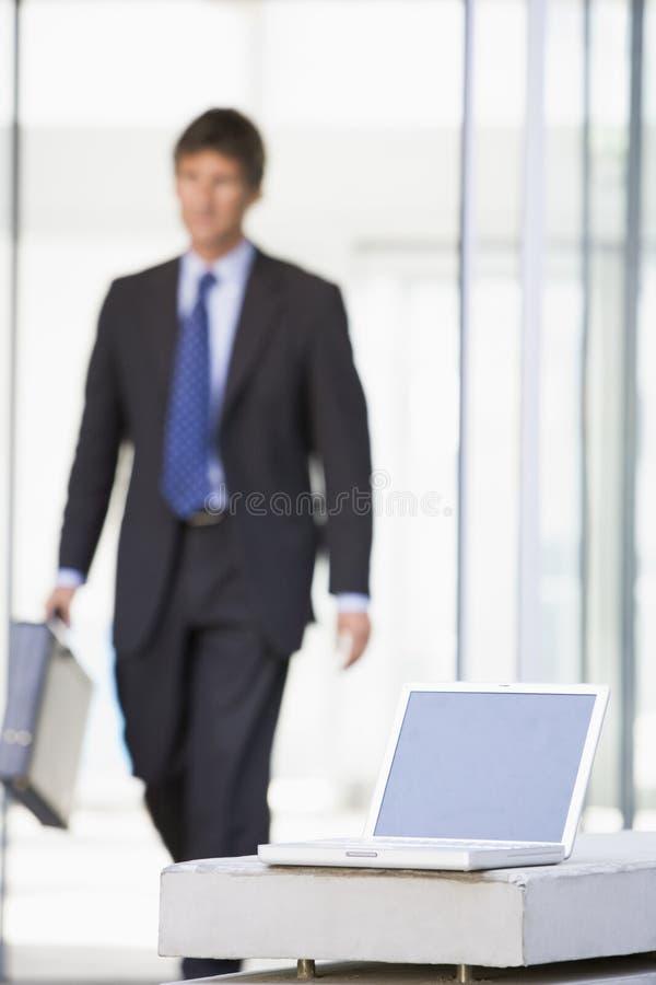 Portátil que senta-se na entrada do escritório com homem de negócios foto de stock royalty free