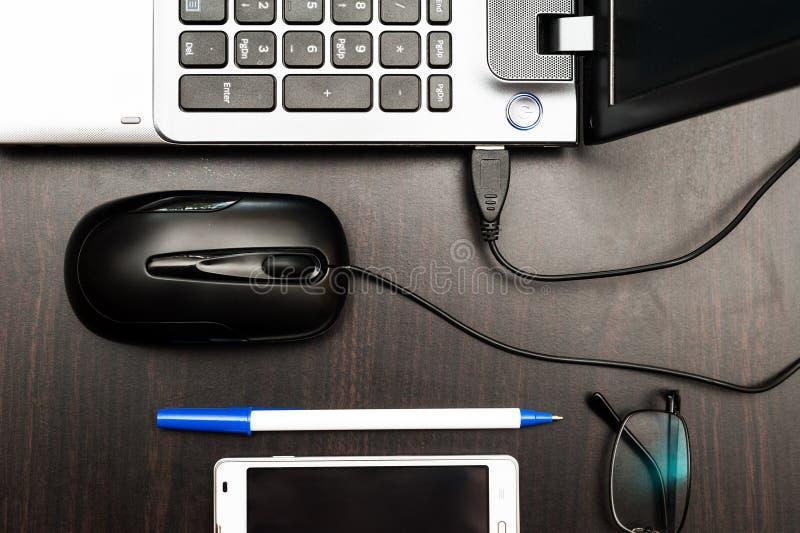 Portátil, rato do computador, telefone celular, vidros e pena na tabela imagem de stock royalty free