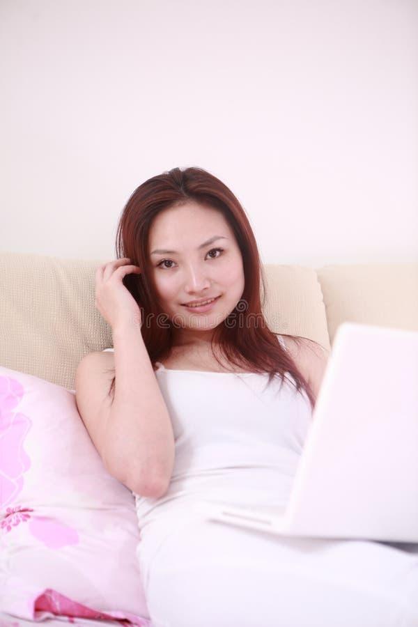 Portátil 'sexy' do uso da mulher na cama fotos de stock royalty free