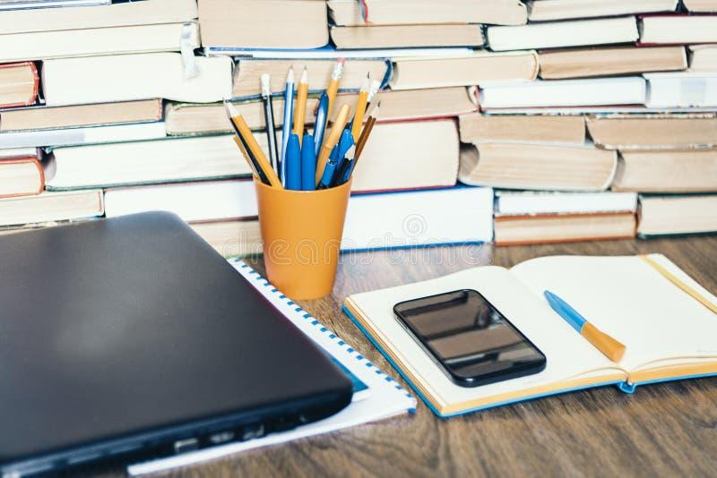 Portátil, smartphone, pilha de livros, caderno e lápis no suporte plástico alaranjado na tabela de madeira, fundo do conceito da  fotos de stock royalty free