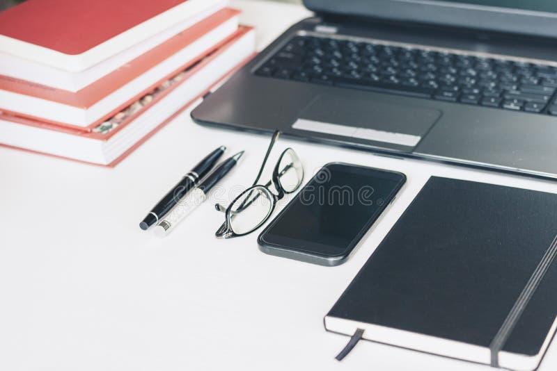 Port?til, smartphone, pilha de livros, penas, vidros, caderno na tabela de madeira, fundo do conceito do escrit?rio da educa??o e fotografia de stock