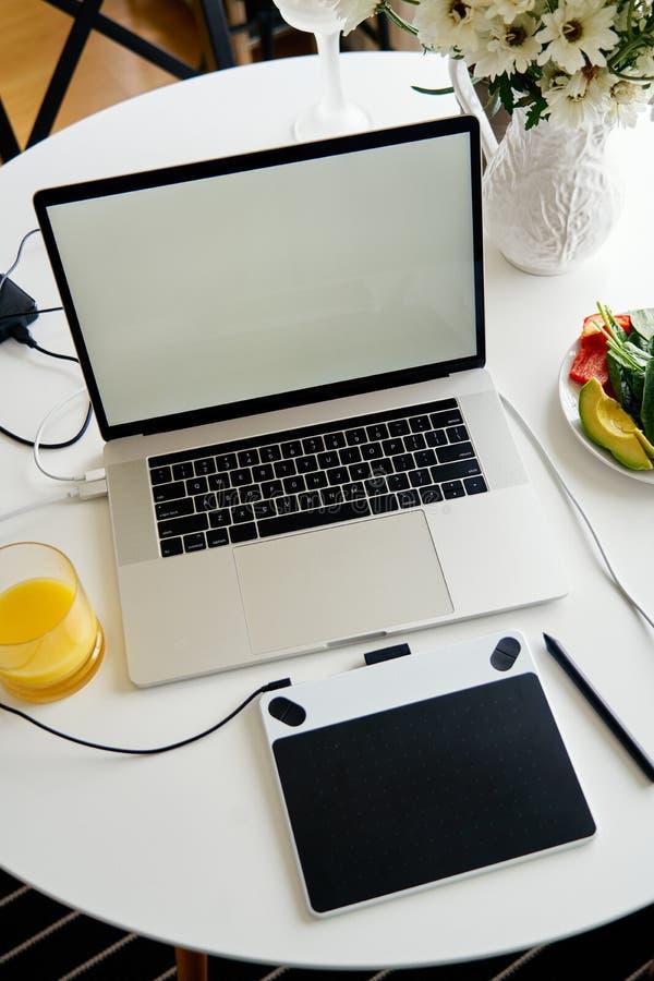 Portátil, tabuleta de gráficos e café da manhã abertos com suco na tabela branca, tela vazia para o projeto do modelo foto de stock