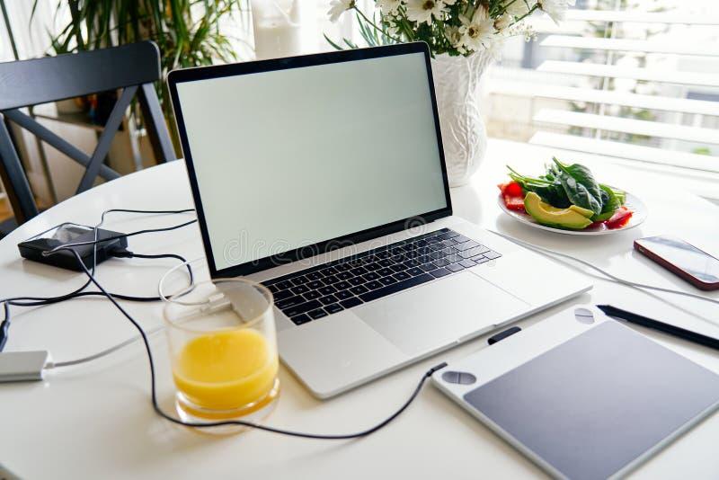 Portátil, tabuleta de gráficos e café da manhã abertos com suco na tabela branca, tela vazia para o projeto do modelo fotos de stock royalty free