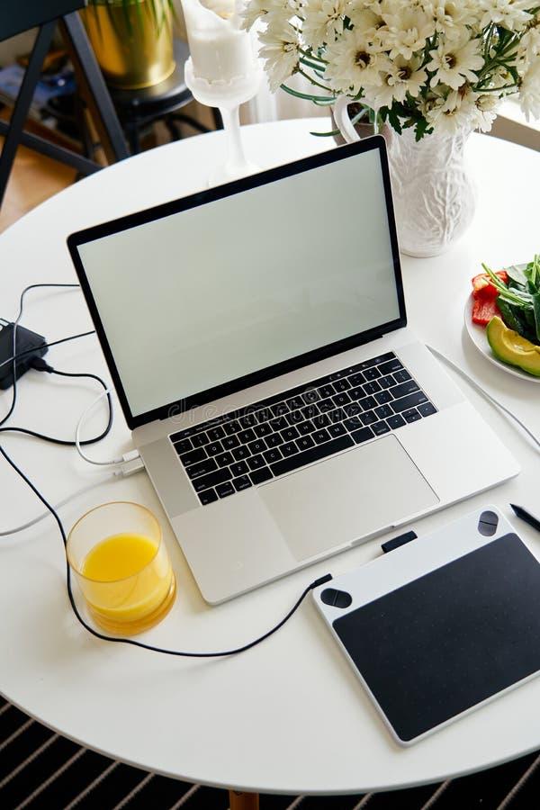 Portátil, tabuleta de gráficos e café da manhã abertos com suco na tabela branca, tela vazia para o projeto do modelo fotografia de stock royalty free