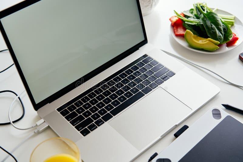 Portátil, tabuleta de gráficos e café da manhã abertos com suco na tabela branca, tela vazia para o projeto do modelo foto de stock royalty free