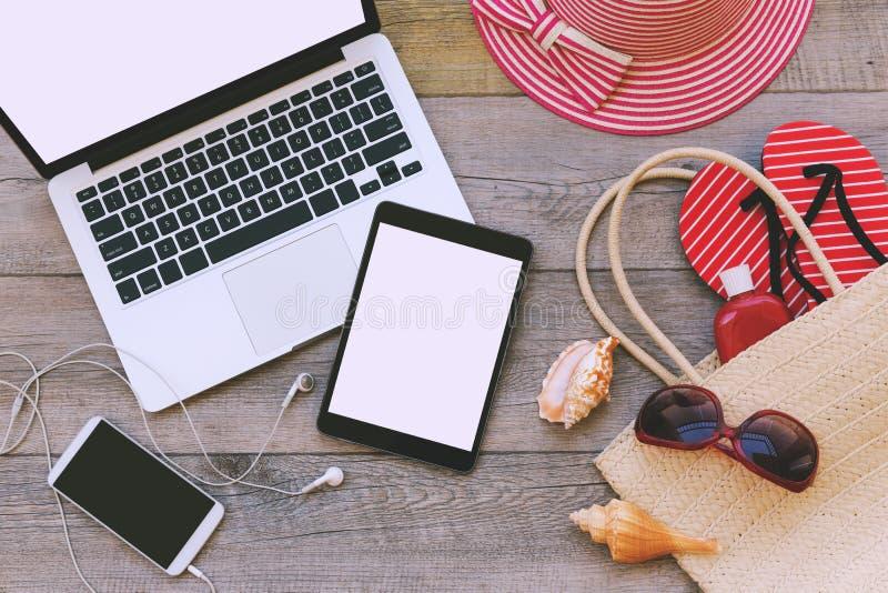 Portátil, tabuleta digital e telefone esperto com artigos da praia sobre o fundo de madeira Vista de acima fotografia de stock royalty free
