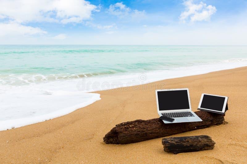 Portátil, tabuleta e smartphone na praia nas horas de verão fotografia de stock