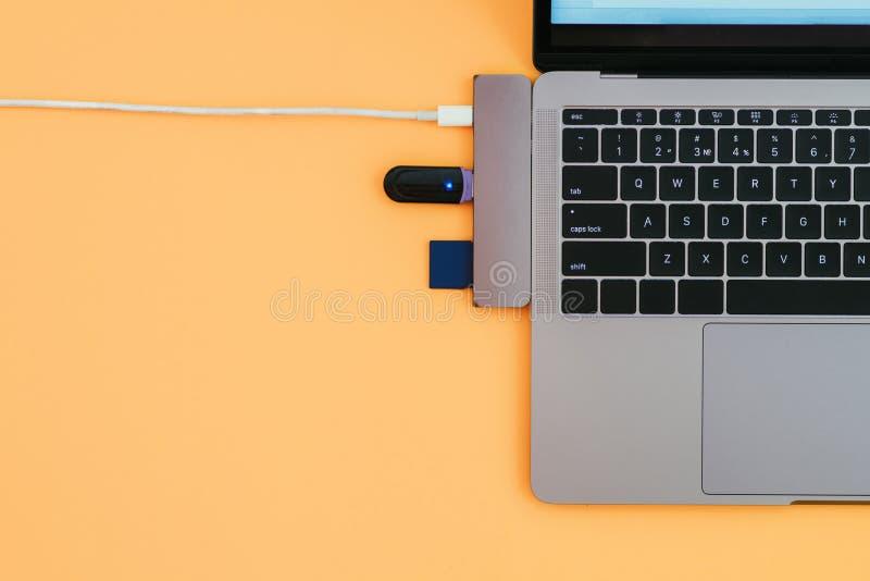 Portátil, tipo-c modernos adaptador de USB com um flash e o carregamento no fundo alaranjado fotografia de stock