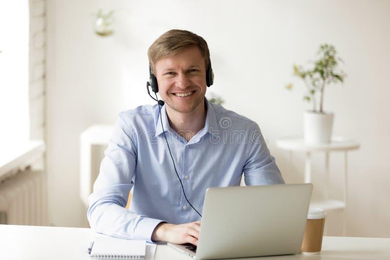 Portátil vestindo do uso dos auriculares do homem de negócios que levanta olhando a câmera imagem de stock