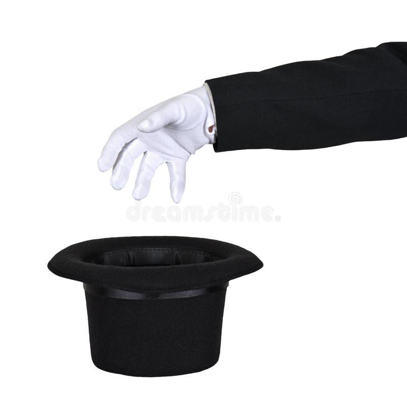 Portée de magicien dans le premier chapeau magique d'isolement photographie stock