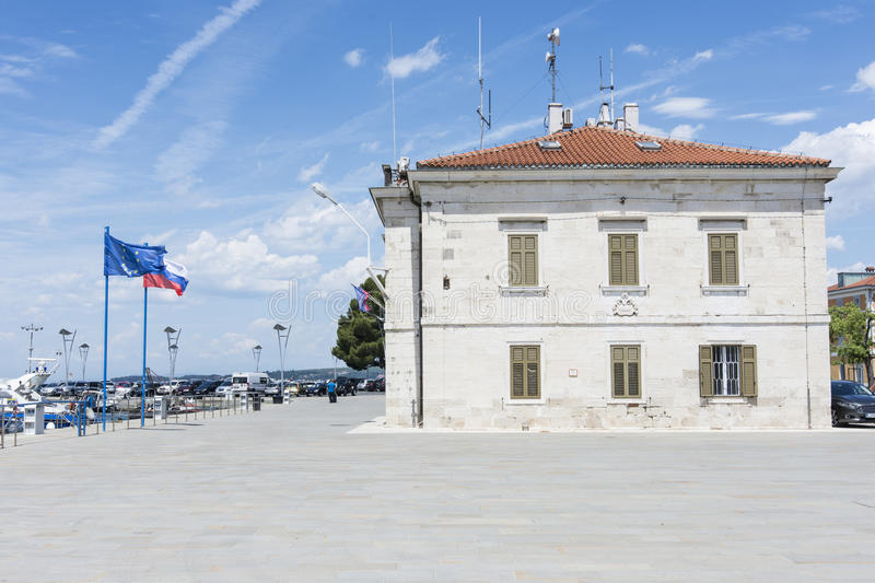 Port authorities palace in Koper, Slovenia. The port authorities building with European and Slovenian flags waving stock photography