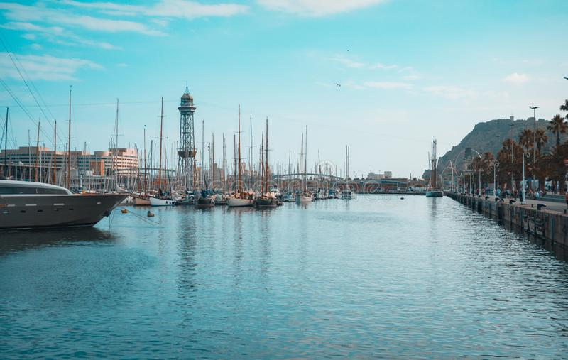 Barcelona marina port with teleferic tower and boats, teal and orange view. Port of Barcelona, Spain. Yachts, sailing boats and old big tower. Teal and orange royalty free stock photos