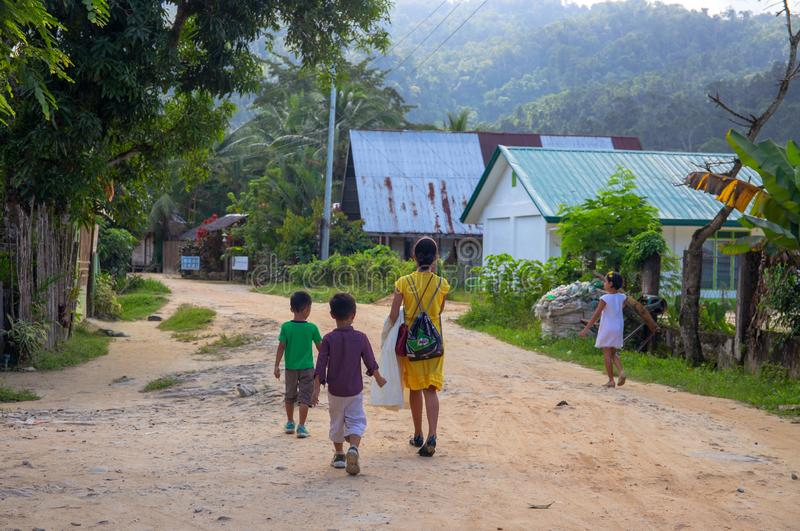 Port Barton, Philippines - 23 Nov 2018: Woman and children on dusty road. Filippino family on rustic village street stock images