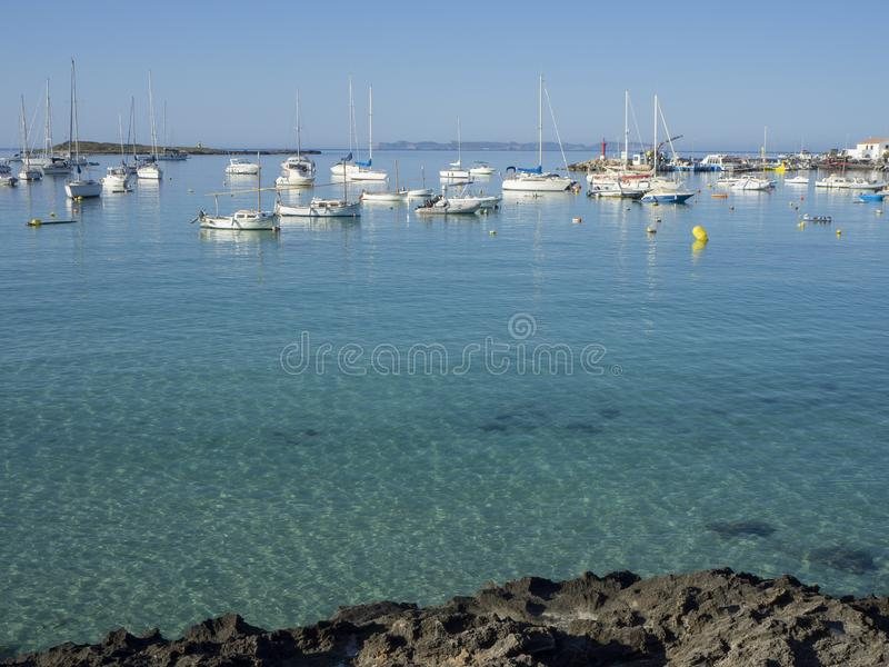 Port de索勒,马略卡,西班牙 灯塔和岩石在村庄附近从小船 库存图片