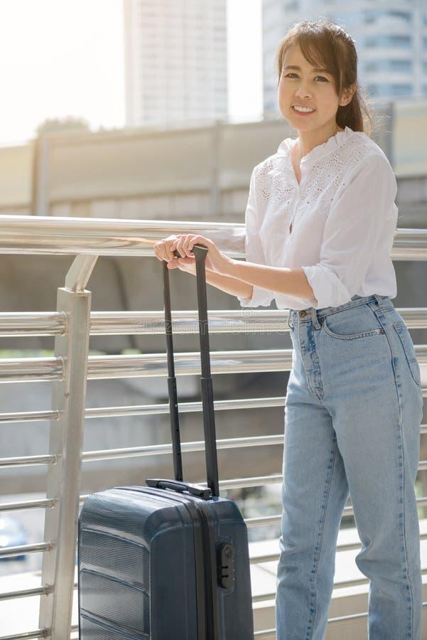 Port de jeune femme occasionnel avec son bagage photographie stock