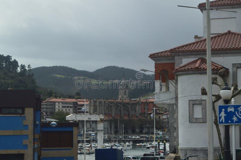 Port de Lekeitio avec ses bateaux amarrés par Hugo At The Background Views temporel des bâtiments de cette ville de Presious marc image stock