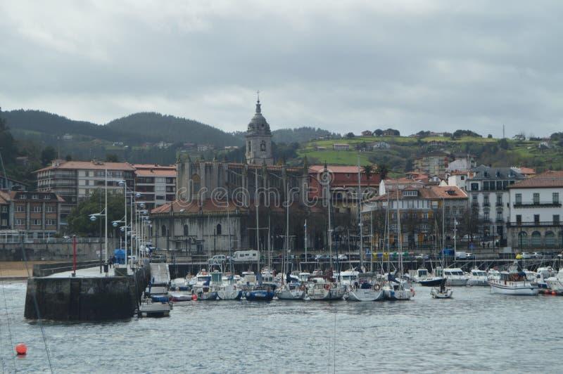 Port de Lekeitio avec ses bateaux amarrés par Hugo At The Background Views temporel des bâtiments de cette ville de Presious marc photos stock