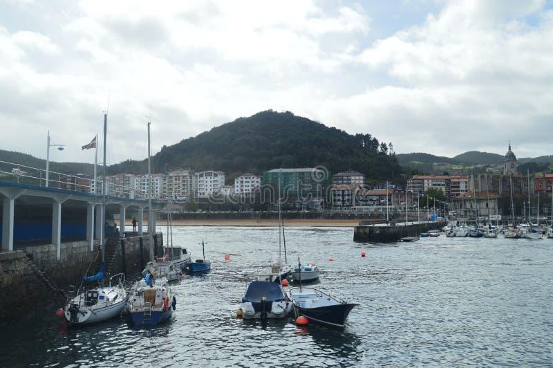 Port de Lekeitio avec ses bateaux amarrés par Hugo At The Background Views temporel des bâtiments de cette ville de Presious marc images stock