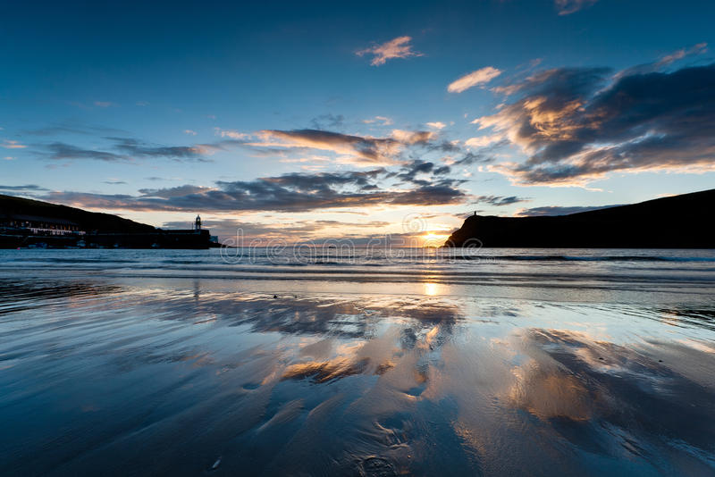 Port Erin beach at sunset. Sunset at Port Erin beach in the Isle of Man with the harbour and Bradda head silhoutetted and clouds reflected on the wet sand royalty free stock images