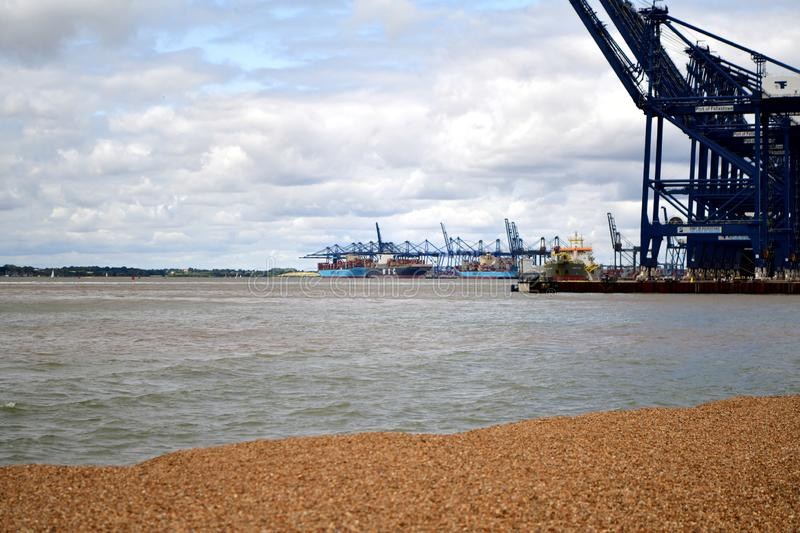 Port in Felixstowe UK. In the background a church tower and a city Tugs lead out a container ship from the port The Port of Felixstowe is Britain's stock photo
