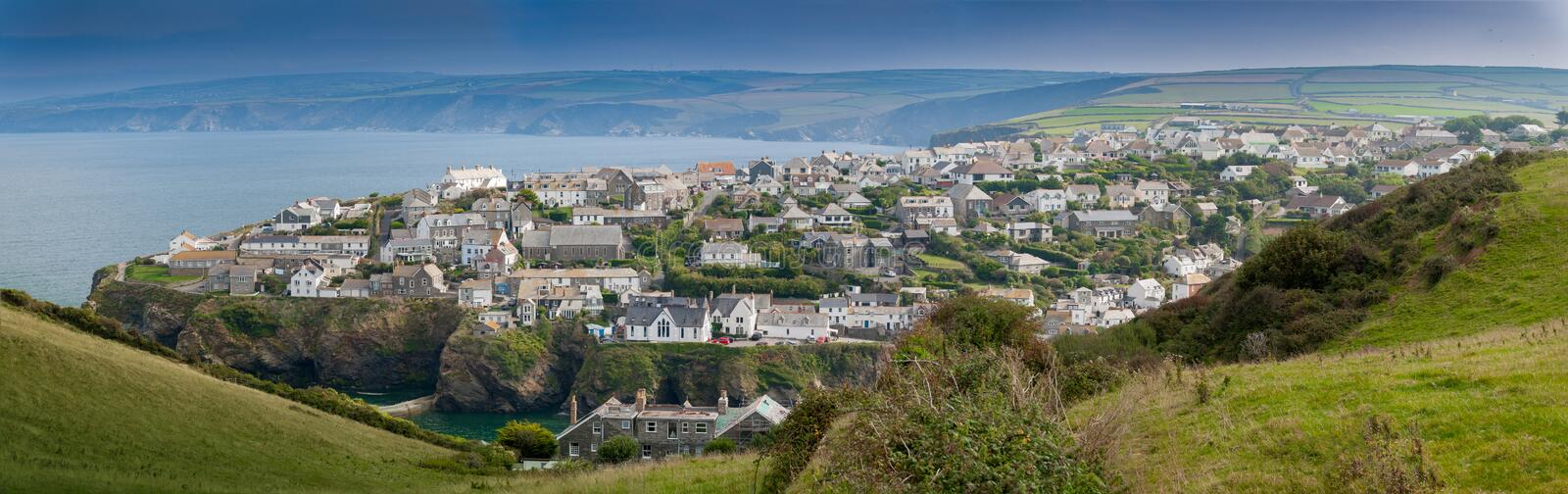 Port Isaac. Panoramic view of Port Isaac in northern Cornwall. View from the coast path approaching from the west of the village stock images