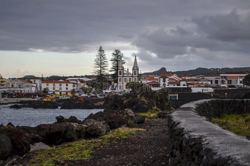 Port la città con la chiesa bianca su una costa della lava dell'isola di Pico immagine stock