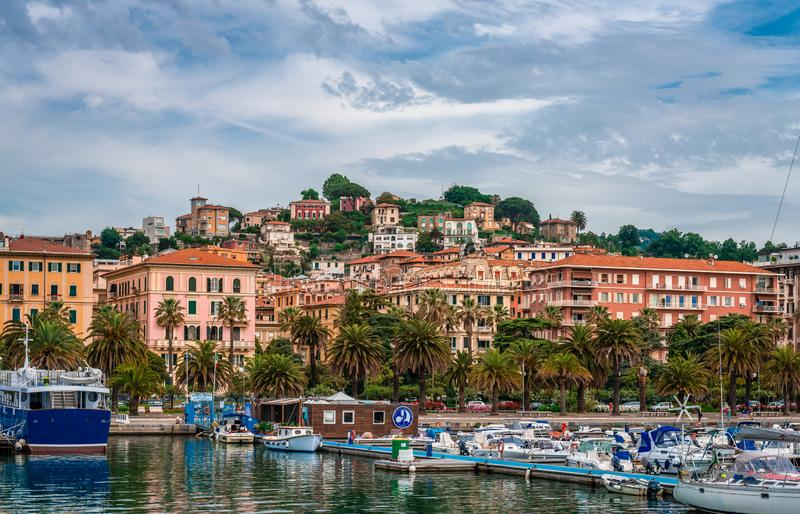 The port of La Spezia. La Spezia / Italy - May 27 2018: View of the port of the city, as seen from the sea, with lot of boats, palm trees and traditional houses royalty free stock photography
