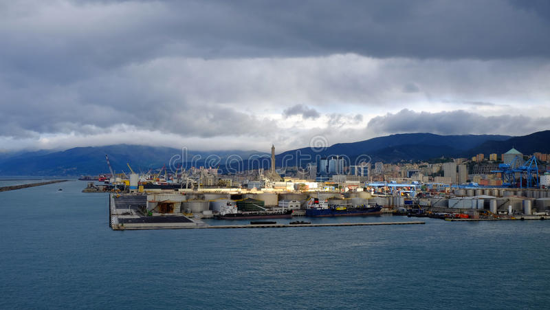 Port and the Lighthouse of Genoa in a cloudy day. View on the port of Genoa, the lighthouse and the hills in a cloudy day. Liguria, Italy royalty free stock images