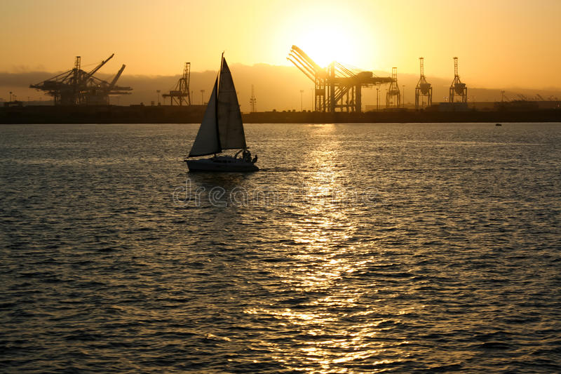 Port of Long Beach Sailboat. A sailboat leaving the Port of Long Beach in southern California during sunset royalty free stock photos
