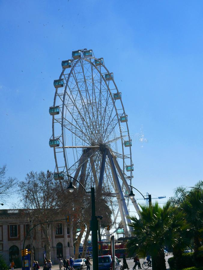 The Ferris Wheel amongst the Harbour Buildings of Malaga in Andalucia Spain. The port of Malaga is a busy harbour dealing with international trade to Southern royalty free stock photography