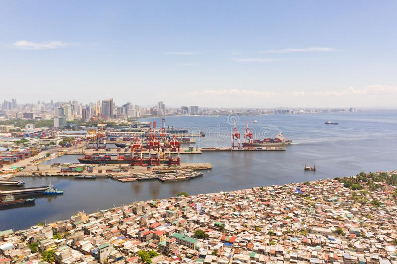 Port in Manila, Philippines. Sea port with cargo cranes. Cityscape with poor areas and business center in the distance. View from above. Asian metropolis royalty free stock photography