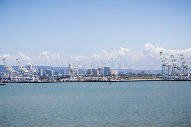 Port of Oakland cranes, Oakland downtown in the background, San Francisco bay area, California stock image
