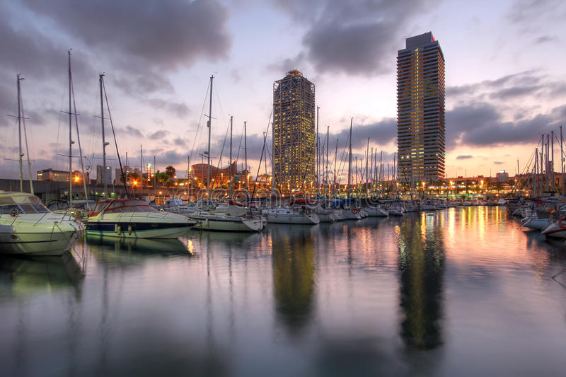 Port Olimpic, Barcelona, Spain. Twin skyscrapers towering over the marina in Port Olimpic (Olympic Harbor), Barcelona, Spain at sunset royalty free stock photos